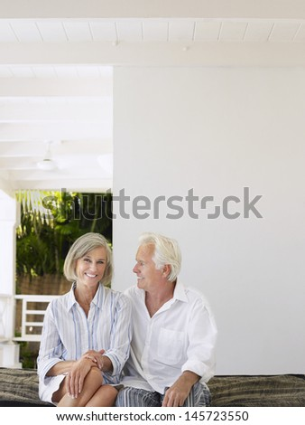 Happy middle aged couple sitting on verandah - stock photo