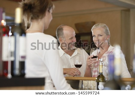 Happy middle aged couple tasting wine with merchant in foreground - stock photo