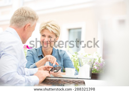 Happy middle-aged couple using cell phone at sidewalk cafe - stock photo