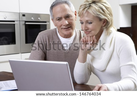 Happy middle aged couple using laptop at kitchen table - stock photo