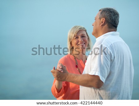 Happy middle-aged couple wearing casual summer clothes while dancing outdoors on a romantic song