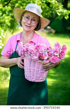 Happy middle aged female gardener in hat and apron smiling while holding basket of roses in yard during summer. - stock photo