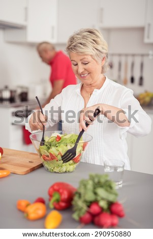 Happy Middle Aged Housewife Preparing Healthy Fresh Vegetable Salad on a Glass Bowl at the Kitchen - stock photo