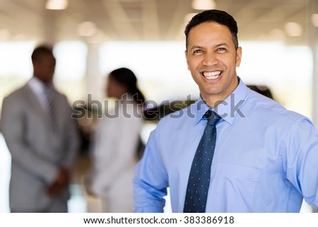 happy middle aged male vehicle sales consultant in showroom - stock photo