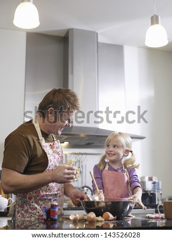 Happy middle aged man and daughter baking in kitchen - stock photo
