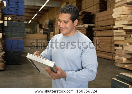 Happy middle aged man checking lumber in warehouse - stock photo