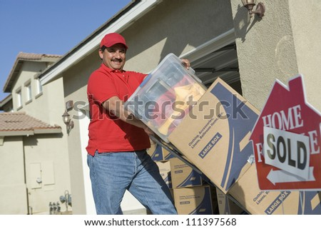 Happy middle aged man delivering cardboard boxes into a new house