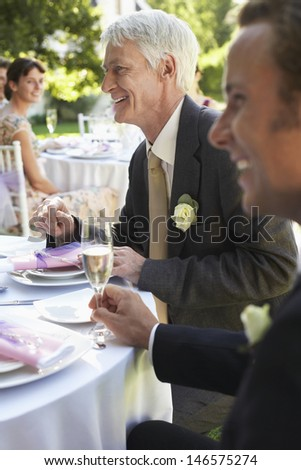 Happy middle aged man with guests in wedding reception - stock photo