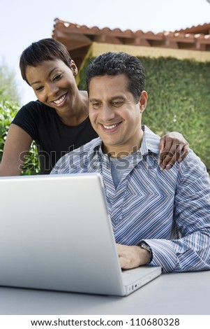 Happy middle aged man with woman working on laptop