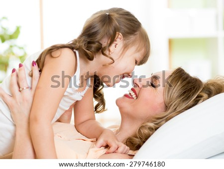 Happy middle-aged mom playing with her kid daughter in bed enjoying  sunny morning in home bedroom - stock photo