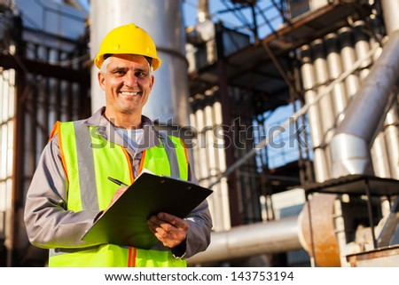 happy middle aged oil industry worker in refinery plant - stock photo