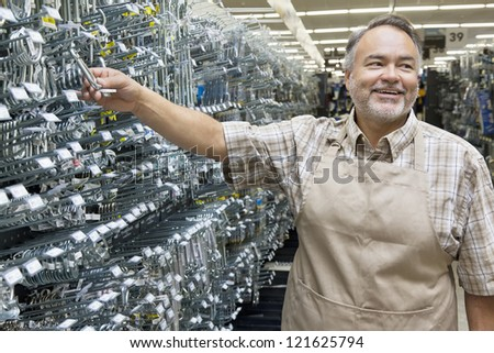 Happy middle-aged salesperson holding metallic equipment while looking away in hardware store - stock photo