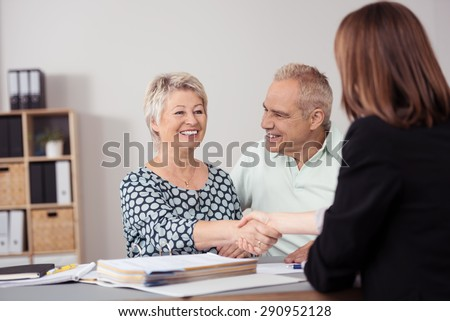 Happy Middle Aged Wife beside her Husband Shaking Hands to a Female Business Agent at the Table. - stock photo