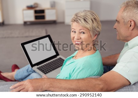 Happy Middle Aged Wife with Laptop Computer, Sitting on the Couch Next to her Husband and Smiling at the Camera. - stock photo