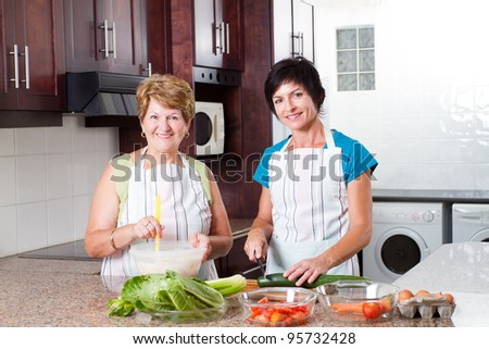 happy middle aged woman cooking with senior mother in kitchen - stock photo
