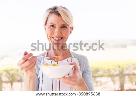 happy middle aged woman eating salad at home - stock photo
