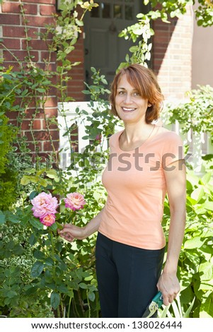 Happy middle aged woman gardening and pruning rose bush with garden shears