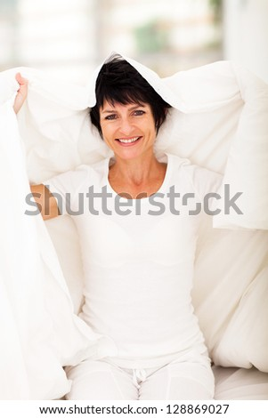 happy middle aged woman having fun with duvet in bedroom