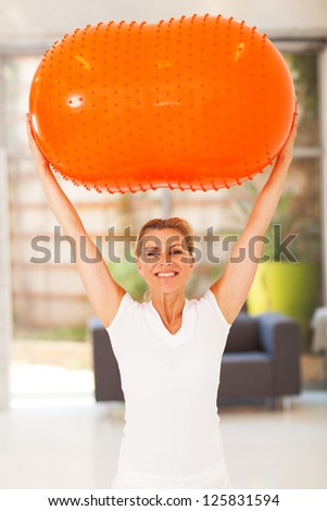 happy middle aged woman holding an exercise ball - stock photo