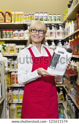 Happy middle-aged woman holding can while looking away - stock photo