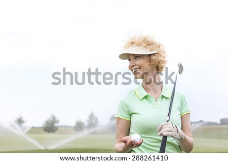 Happy middle-aged woman looking away while holding golf club and ball - stock photo