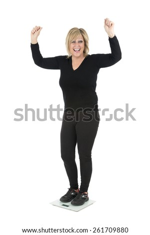 Happy middle aged woman on a weighing scale against a white background - stock photo