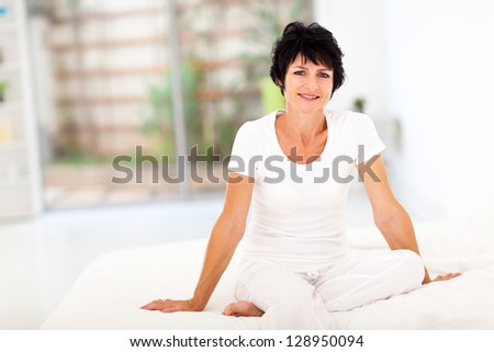 happy middle aged woman sitting on bed at home - stock photo