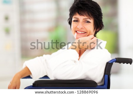 happy middle aged woman sitting on wheelchair and recovering from sickness