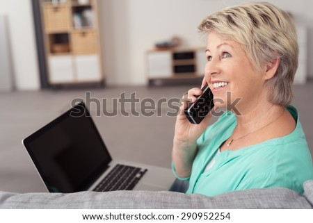 Happy Middle Aged Woman with Laptop Computer, Sitting at the Couch While Talking to Someone on Phone. - stock photo