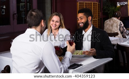 Happy middle class couple and friend enjoying food in cafe