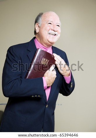 Happy minister holding the Bible and preaching a message of love. - stock photo