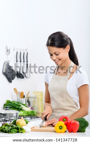 Happy mix race woman cooking and preparing food in the kitchen wearing a apron - stock photo