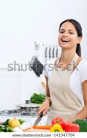 Happy mix race woman laughing while cooking and preparing food in the kitchen wearing a apron - stock photo