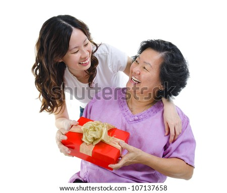 Happy Mixed race Asian mother receiving present from her daughter - stock photo