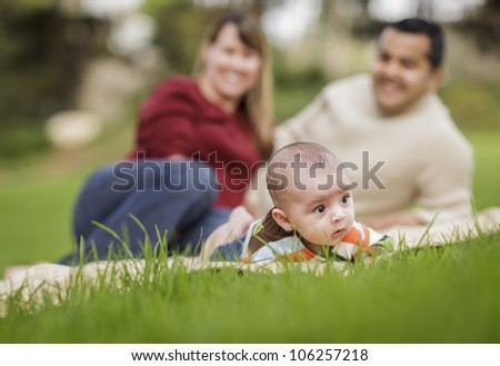 Happy Mixed Race Baby Boy and Parents Playing Outdoors in the Park. - stock photo