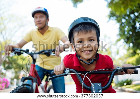 Happy mixed-race boy and his father cycling in the park