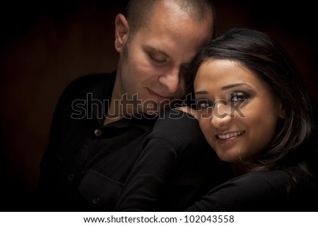 Happy Mixed Race Couple Flirting with Each Other Portrait Against A Black Background. - stock photo