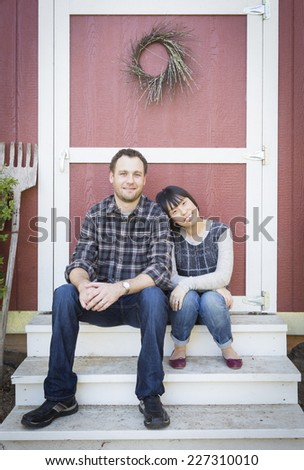 Happy Mixed Race Couple Relaxing on the Steps of Their Barn. - stock photo