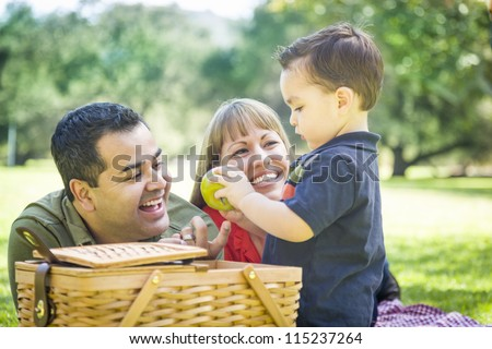 Happy Mixed Race Family Enjoy a Picnic At The Park. - stock photo