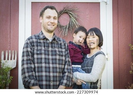 Happy Mixed Race Family Having Fun Outside on the Grass. - stock photo