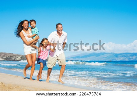 Happy Mixed Race Family of Four on the Beach - stock photo