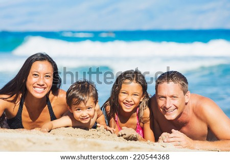 Happy Mixed Race Family of Four Playing and Having Fun on the Beach in the Sand. Tropical Beach Family Vacation. - stock photo