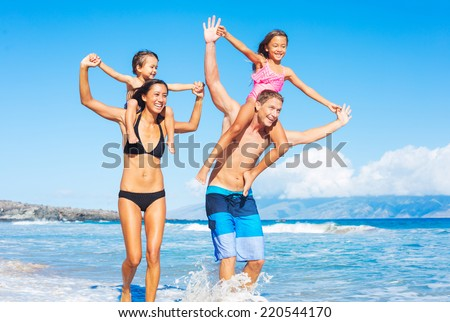 Happy Mixed Race Family of Four Playing and Having Fun on the Beach. Tropical Beach Family Vacation. - stock photo