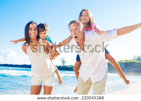 Happy Mixed Race Family of Four Playing on the Beach - stock photo