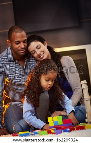 Happy mixed race family sitting on floor at home, father and mother watching little girl playing, smiling. - stock photo