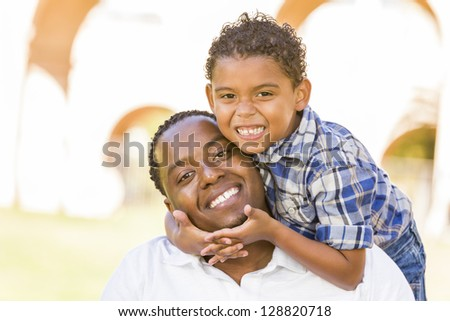 Happy Mixed Race Father and Son Playing Piggyback in the Park. - stock photo
