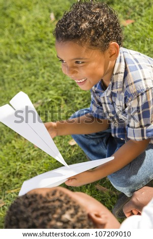 Happy Mixed Race Father and Son Playing with Paper Airplanes in the Park. - stock photo