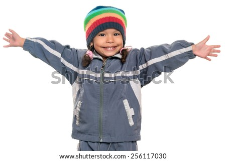 Happy mixed race little girl wearing a colorful beanie hat offering a hug with wide open arms isolated on white - stock photo