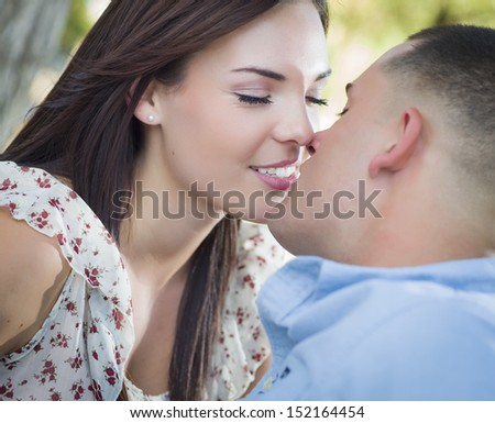Happy Mixed Race Romantic Couple Kissing in the Park. - stock photo