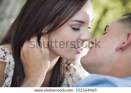 Happy Mixed Race Romantic Couple Kissing in the Park.